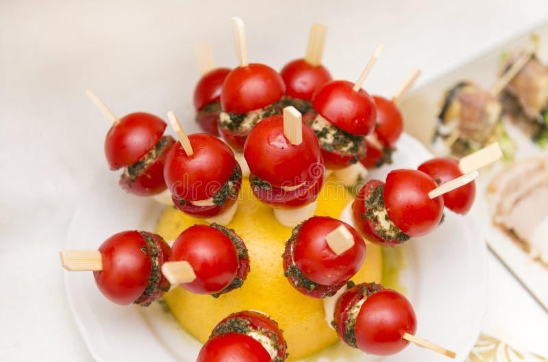Apéritif au buffet, tomates avec du fromage sur des bâtons, brochettes photo libre de droits