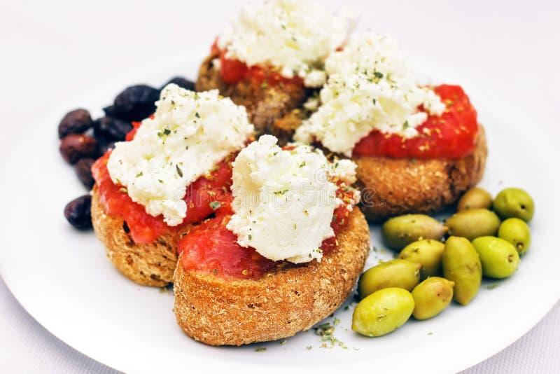 Apéritif crétois - dakos, biscotte avec la sauce tomate, olives et fromage local de staka photo stock