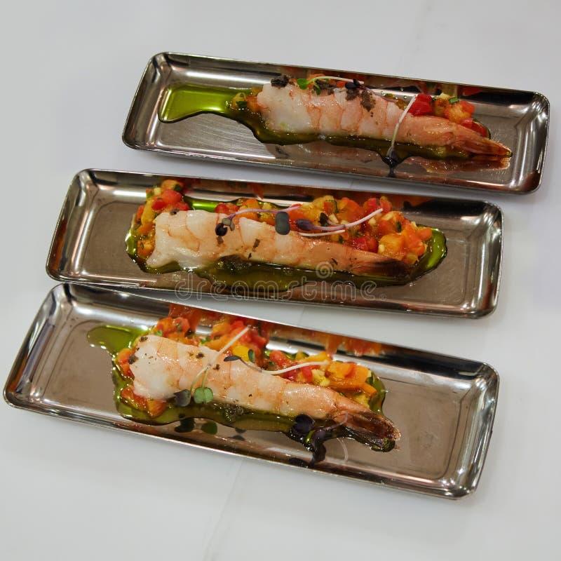 Apéritif délicieux des crevettes avec des légumes dans des plats de chrome photo stock