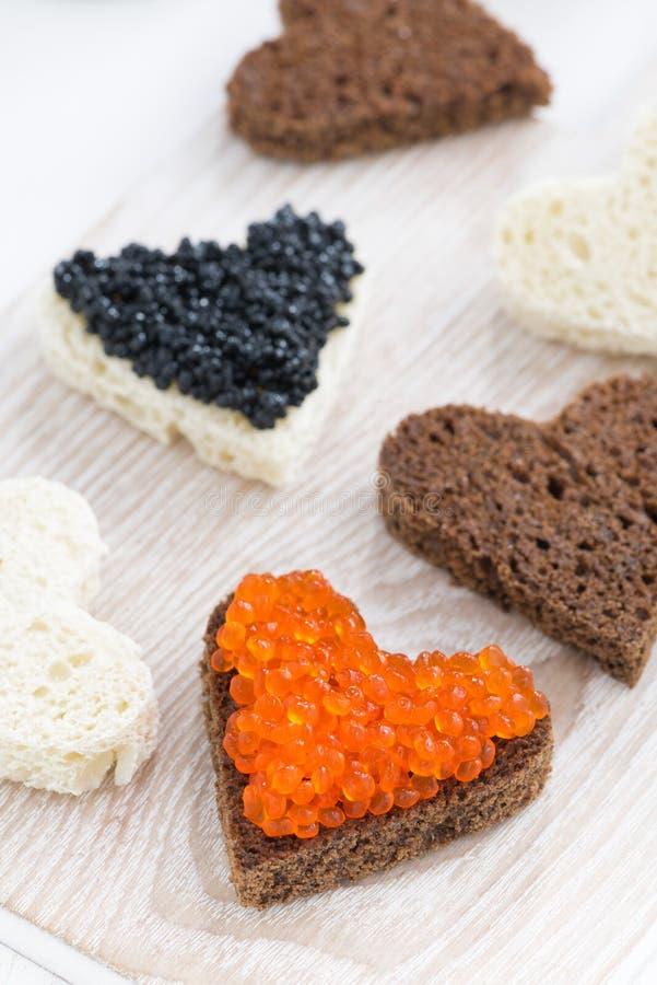 Apéritif de fête - les pains grillés au coeur forment sur le conseil en bois photographie stock libre de droits