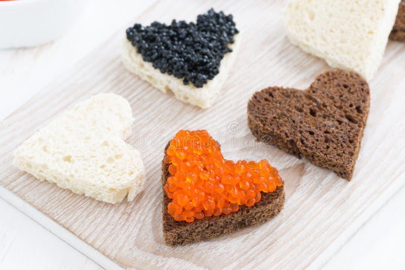 Apéritif de fête - les pains grillés au coeur forment sur le conseil en bois blanc photographie stock