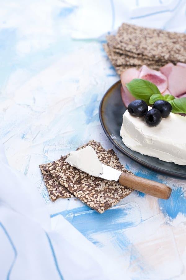Apéritif de fromage et de jambon sur un fond bleu de plat et de lumière L'espace libre pour le texte ou la publicité photographie stock