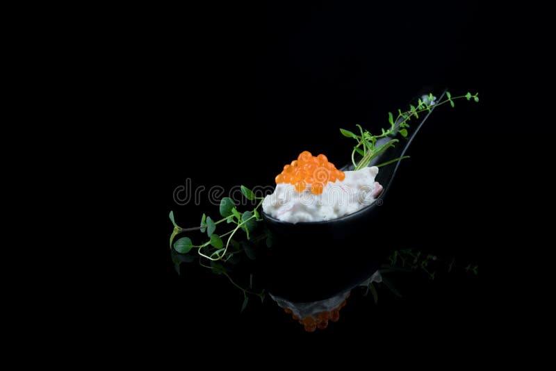 Apéritif de fruits de mer Caviar garni de feuilles vertes, une cuillère isolée sur fond noir avec réflexions images stock