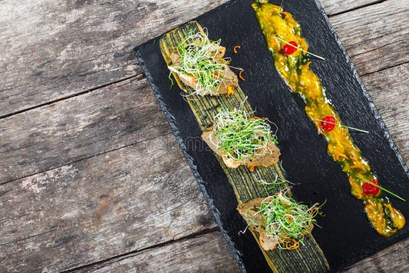 Apéritif de pâté et d'oignon de viande sur le fond en pierre d'ardoise sur la table rustique photographie stock