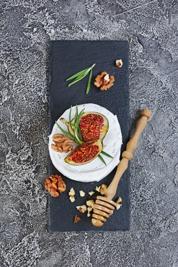 Apéritif gastronome du fromage ou du camembert blanc de brie avec l'épice fraîche de figues, d'écrous, de miel et de romarin sur  photographie stock