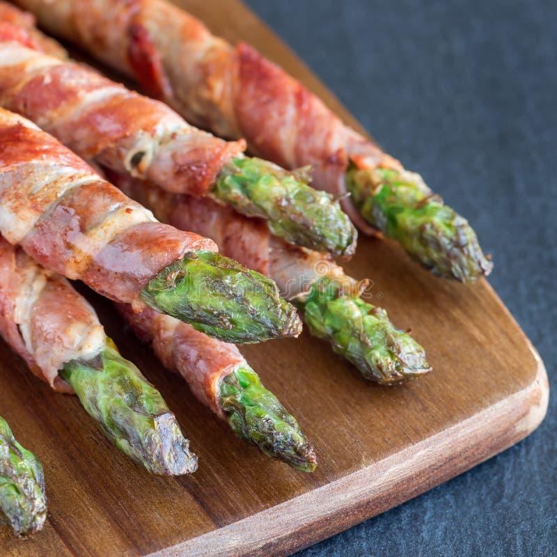 Ap?ritif sain, asperge verte envelopp?e avec le lard sur un conseil en bois, format carr? photographie stock
