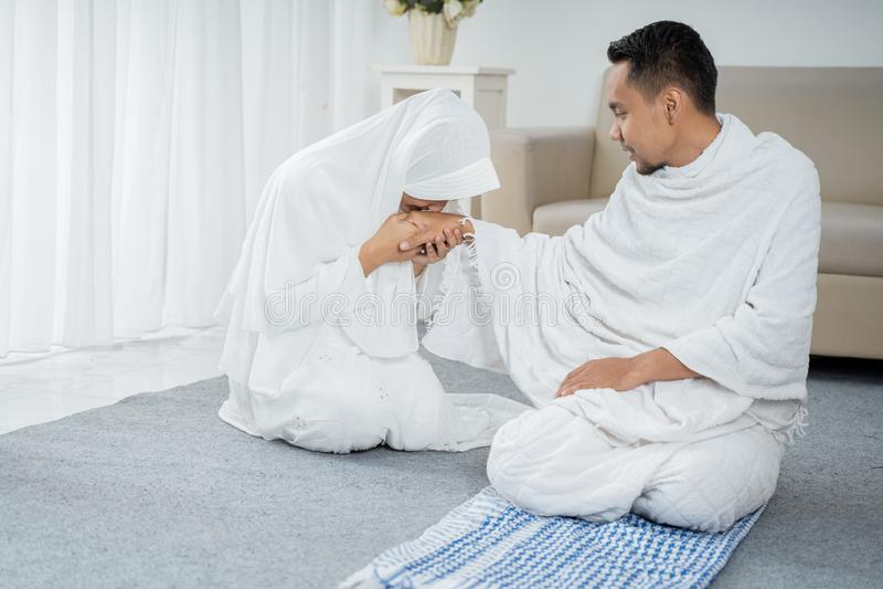 Após a esposa do sholat que beija a roupa tradicional branca vestindo da mão do marido imagem de stock royalty free