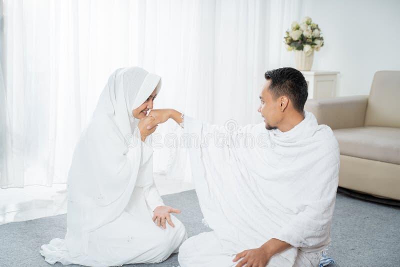 Após a esposa do sholat que beija a roupa tradicional branca vestindo da mão do marido foto de stock royalty free