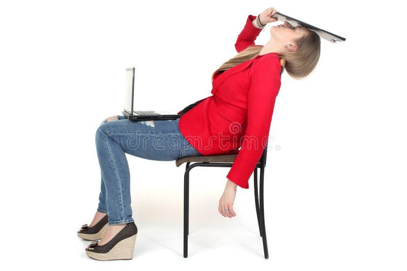 Após o trabalho duro - a mulher relaxa no computador imagens de stock royalty free