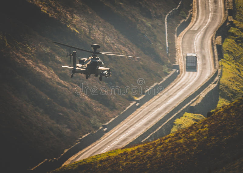 Apache helicopter flying. Army Air Corps AH64 Apache longbow gunship helicopter flying and targeting vehicle on the ground royalty free stock photos
