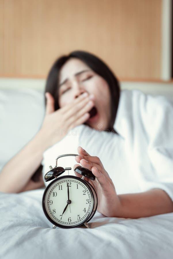 Apagando sano o dormitando el concepto del despertador, mujer hermosa que despierta por la ma?ana en el dormitorio mientras que e fotos de archivo