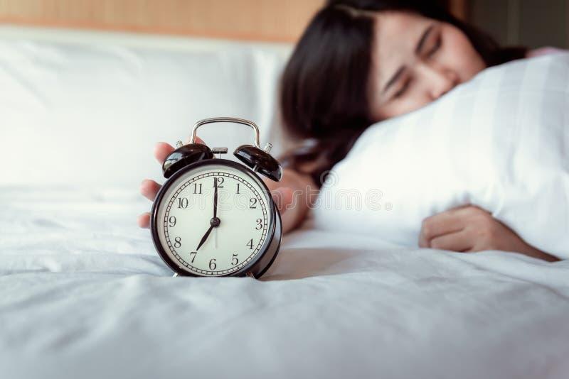 Apagando sano o dormitando el concepto del despertador, mujer hermosa que despierta por la ma?ana en el dormitorio mientras que e foto de archivo