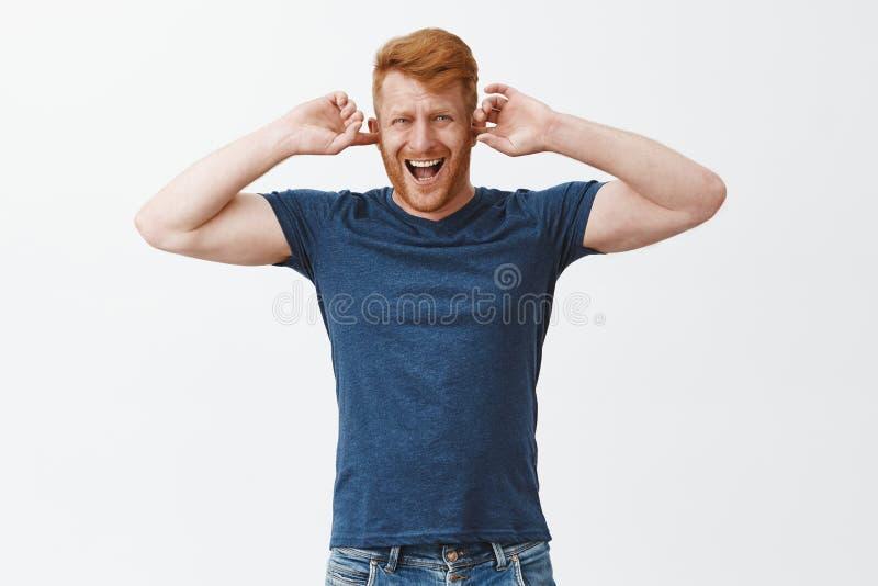 Apague este ruido Hombre atractivo enfadado y descontentado del jengibre con la cerda en la ropa casual, cubriendo los oídos con foto de archivo