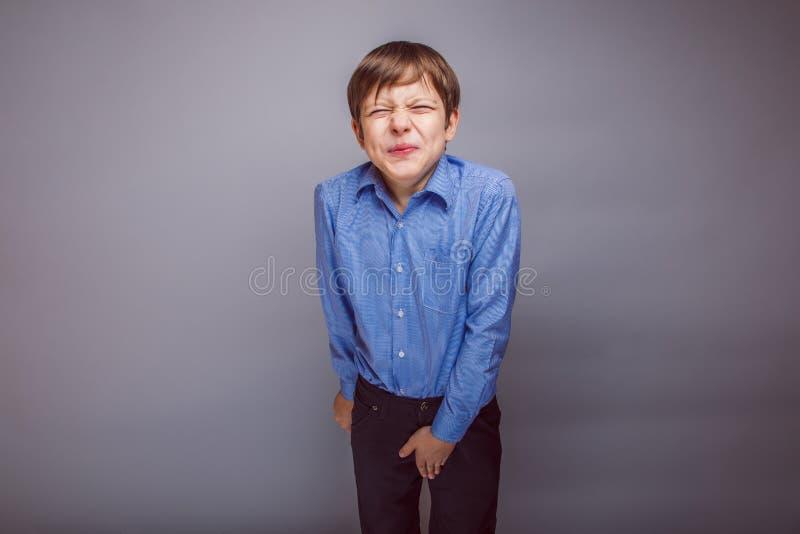A aparência europeia do adolescente do menino encolheu-se sua mão imagens de stock