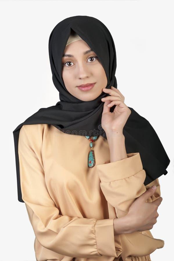 A aparência oriental da mulher bonita nos muçulmanos veste-se em um fundo branco isolado imagem de stock