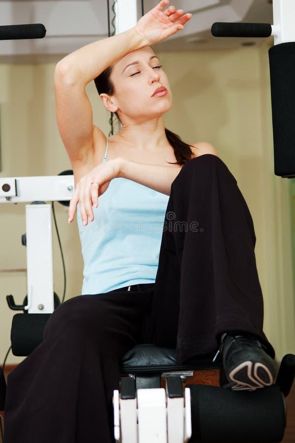 aparata gym obsiadania zmęczona kobieta fotografia stock