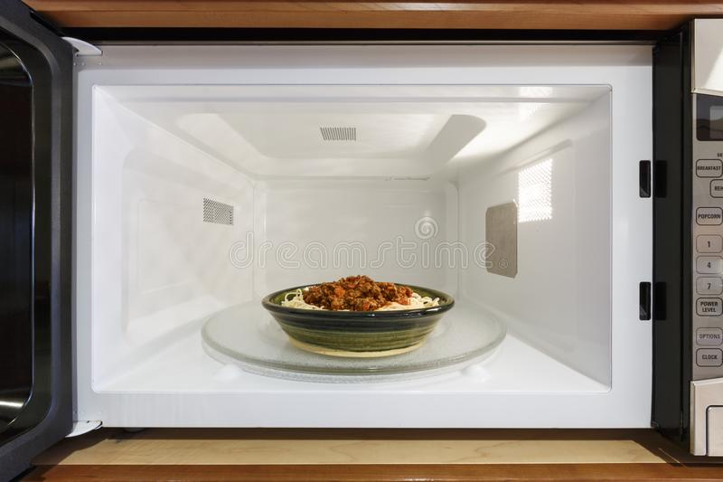 Aparatos electrodomésticos de la cocina que cocinan la comida de los espaguetis de la calefacción en la microonda overn fotografía de archivo libre de regalías