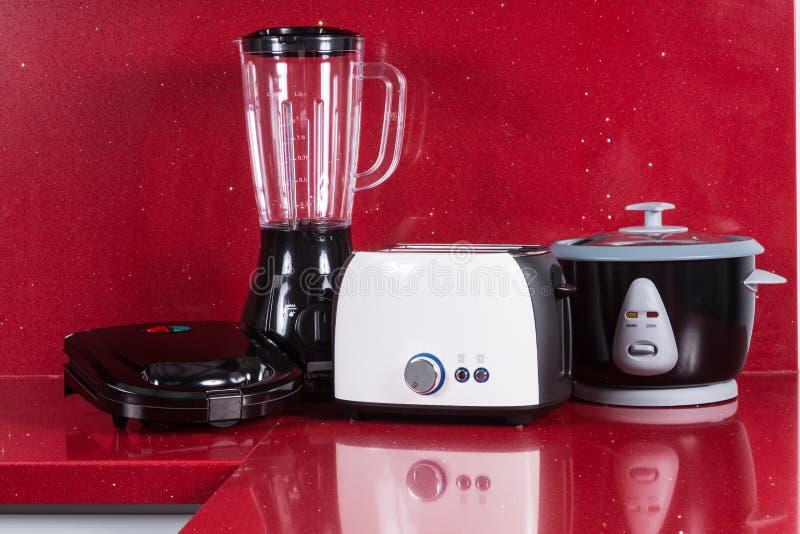 Aparatos electrodomésticos en fondo moderno del rojo de la cocina imágenes de archivo libres de regalías