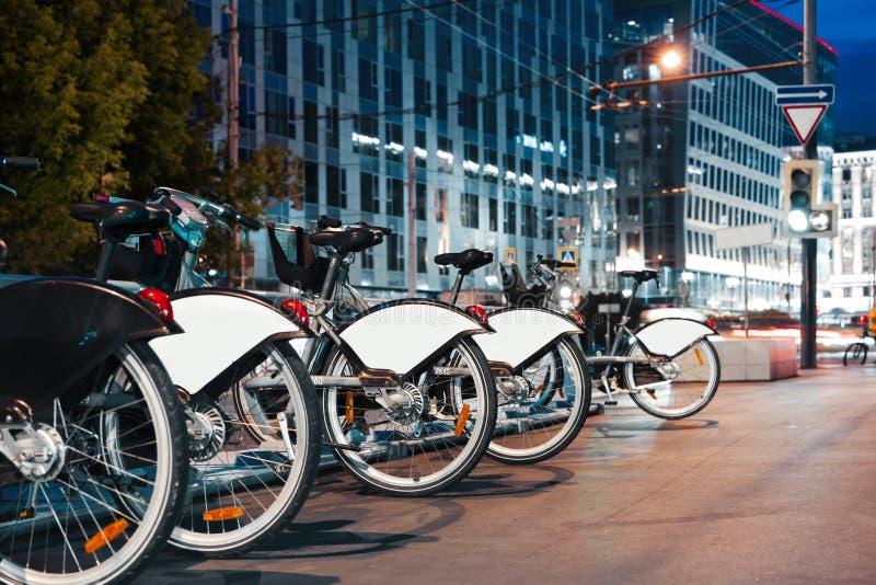 Aparcamiento de la bicicleta en la noche en centro de la ciudad Concepto moderno del transporte fotos de archivo libres de regalías