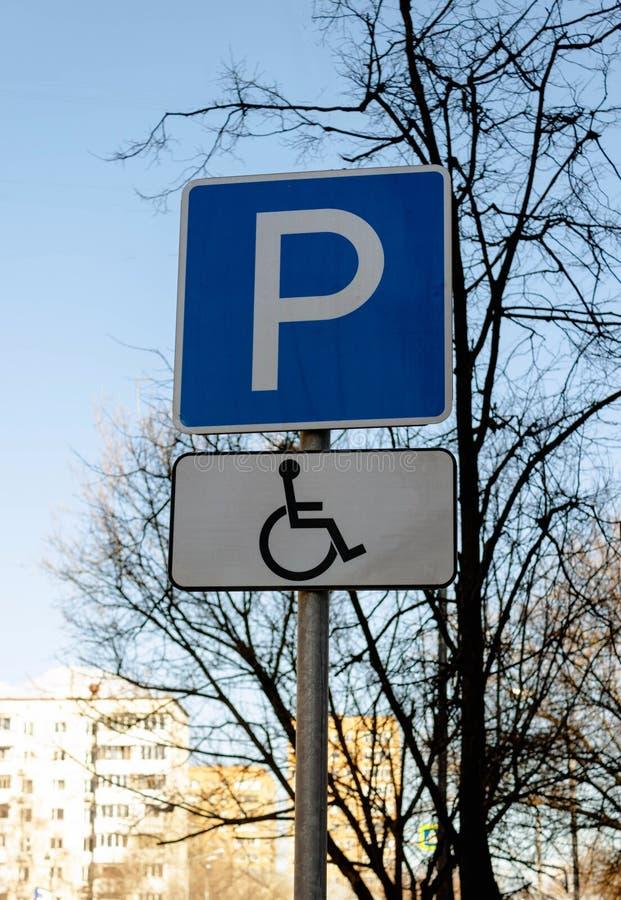 Aparcamiento de la señal de tráfico para discapacitado perjudicado en el cielo azul, árboles y fondo de los edificios fotografía de archivo libre de regalías