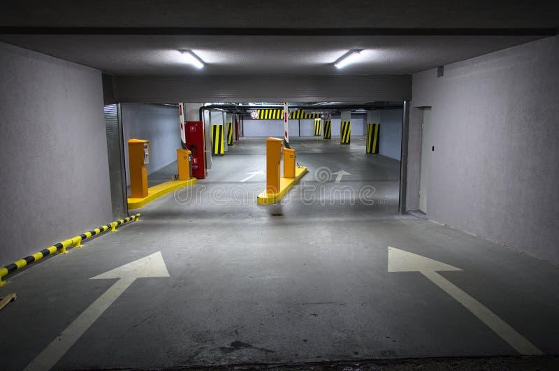 Aparcamiento subterráneo con las flechas y un coche parqueado imagen de archivo