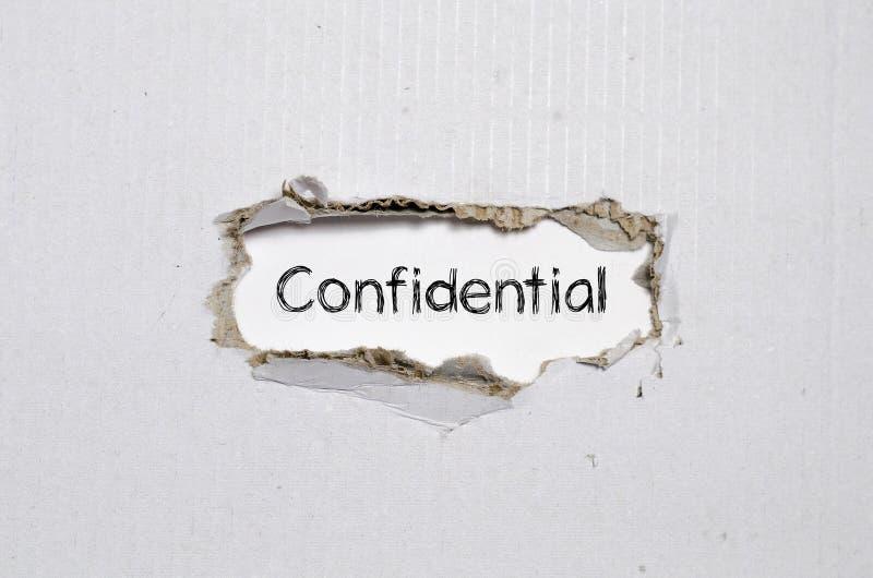 Aparecer confidencial da palavra atrás do papel rasgado imagens de stock royalty free