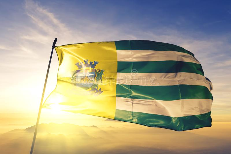 Aparecida de Goiania of Brazil flag waving on the top sunrise mist fog. Aparecida de Goiania of Brazil flag textile cloth fabric waving on the top sunrise mist royalty free stock images