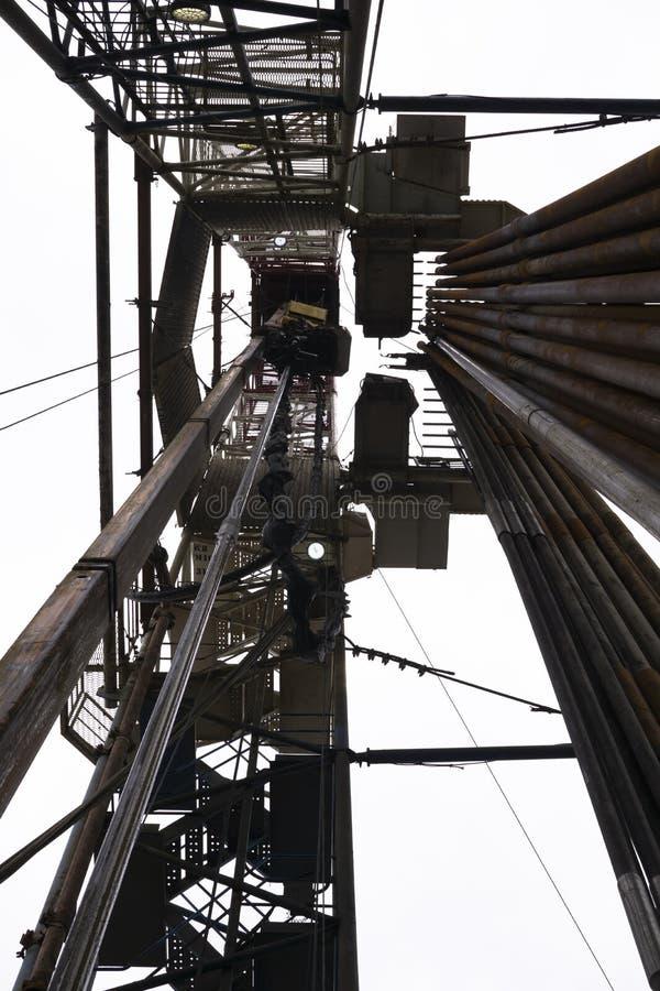 Aparejo de la perforación petrolífera en el campo Campo petrolífero, plataforma de perforación terrestre alrededor con el campo d imagenes de archivo