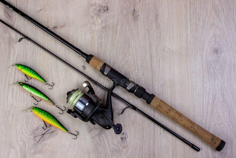 Aparejos de pesca - giro, ganchos y señuelos de la pesca en fondo de madera ligero foto de archivo libre de regalías