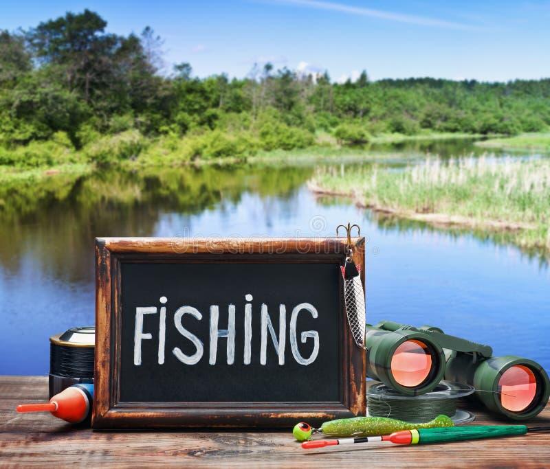 Aparejos de pesca y una pizarra imágenes de archivo libres de regalías
