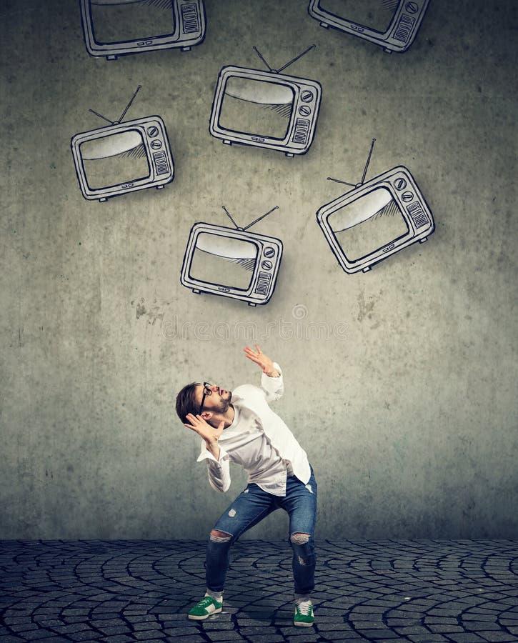 Aparelhos de televisão múltiplos que caem em um homem assustado strssed fotografia de stock
