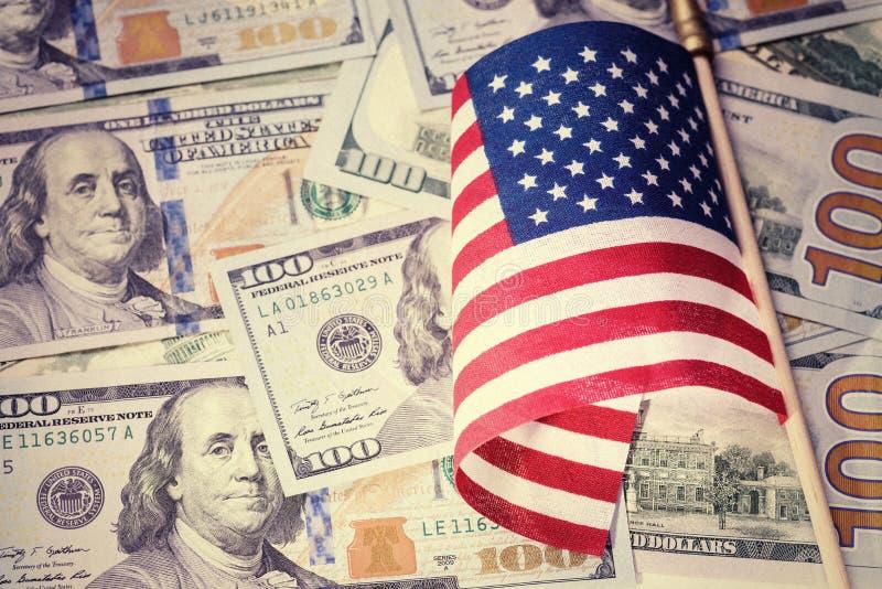 Apariencia vintage Bandera americana en fondo de las cuentas de dólar de EE. UU. Pluma, lentes y gráficos fotos de archivo