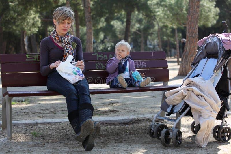 apark婴孩长凳女孩母亲 免版税库存照片