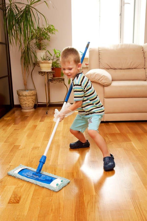 Apartamento da limpeza do rapaz pequeno. Pouco ajudante home. fotos de stock royalty free