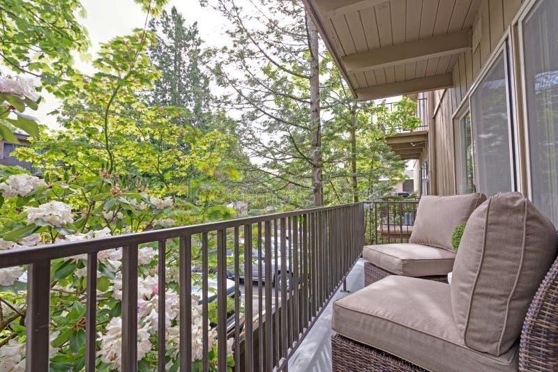 Apartamento de la terraza con las sillas de mimbre imagen de archivo libre de regalías
