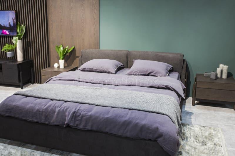 Apartamento-estudio de lujo en un estilo del desván en colores oscuros Área acogedora moderna elegante del dormitorio imagen de archivo