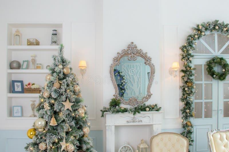 Apartamentos clássicos com uma chaminé branca, uma árvore de abeto decorada, um sofá, umas grandes portas com janelas e um candel imagens de stock royalty free