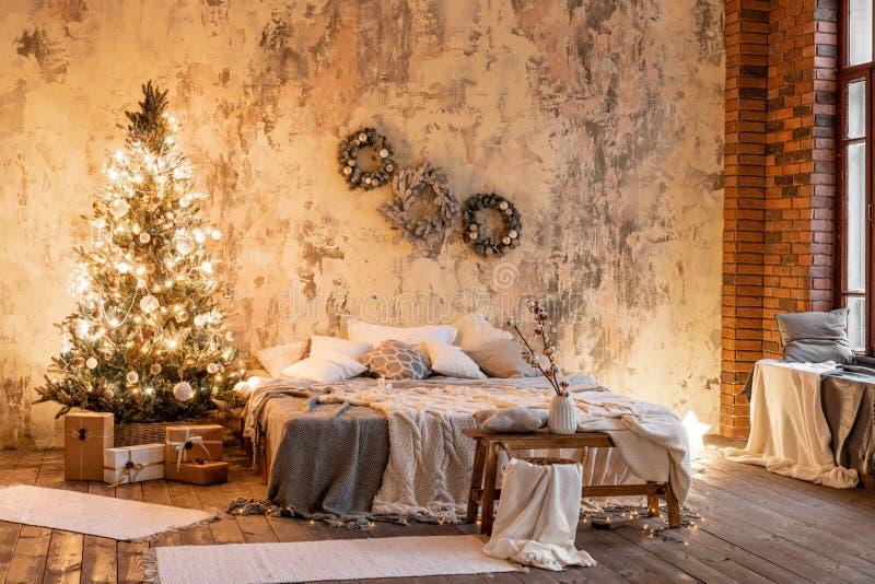 Apartamentos do sótão, parede de tijolo com a grinalda das velas e da árvore de Natal Cama no quarto, grande Windows alto fotos de stock