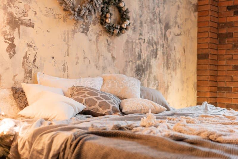 Apartamentos, pared de ladrillo y árbol de navidad del desván Cama en el dormitorio, alto Windows grande imágenes de archivo libres de regalías