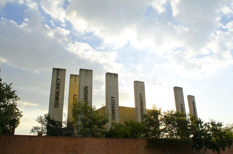 Apartheid museum pillars. Johannesburg, South Africa. Various, stark concrete pillars at the entrance to the Apartheid Museum, depicting the words stock photo