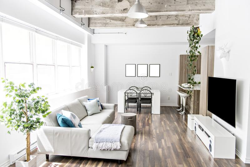 Apartment with big window sofa, table tv and concreate ceiling. An Apartment with big window sofa, table tv and concreate ceiling stock photos