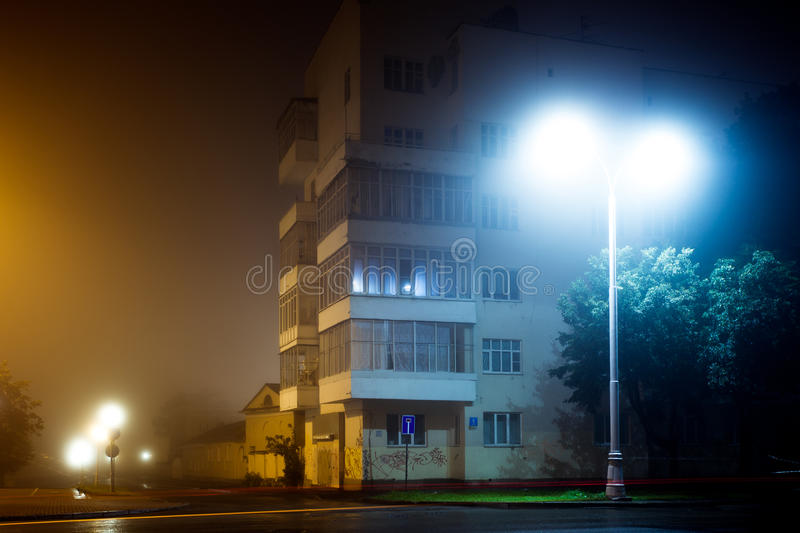Apartment block on empty night city street covered with fog. Blurred city lights glow through misty haze stock photos