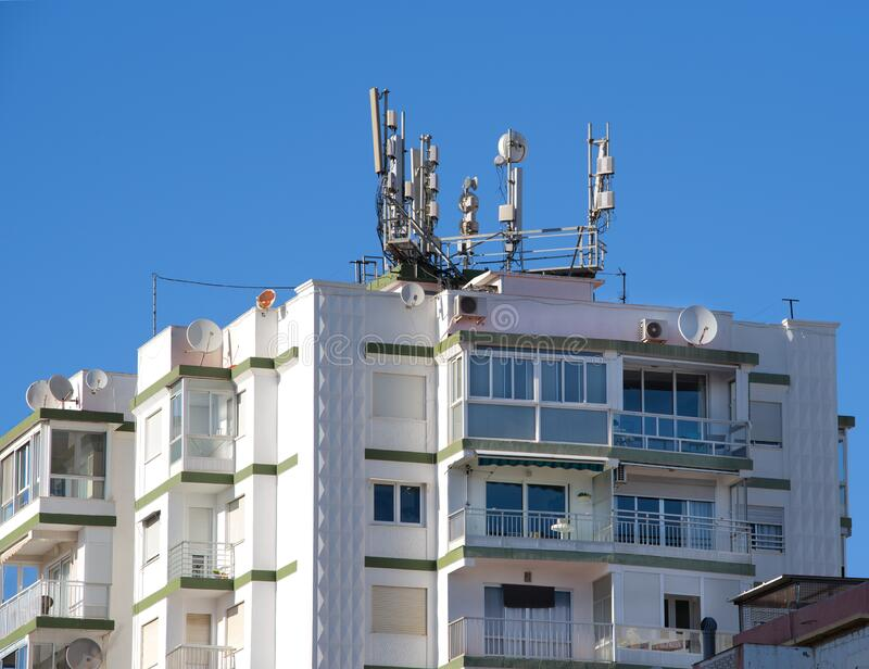 Apartment block, with radio, antennae and mobile masts. An apartment block with various communications equipment, including radio, mobile antennae and masts. A royalty free stock images