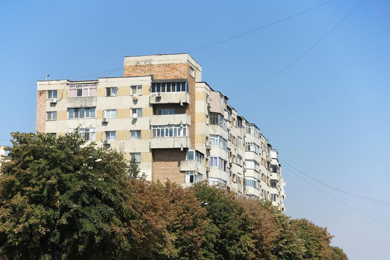 Apartment block rising from the trees. On a clear blue sky stock images