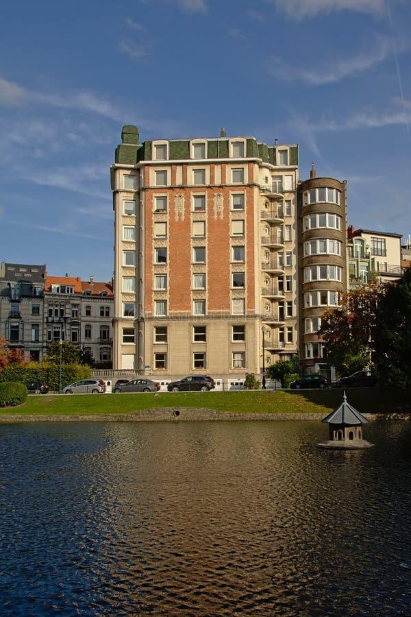Art nouveau apartment building on the embankment of Ixelles lakes and Sainte-Croix church royalty free stock photo
