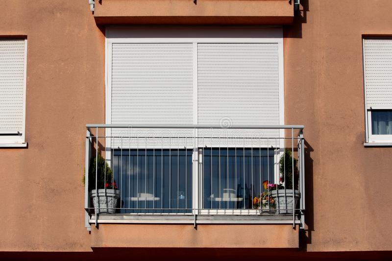 Apartment building balcony with flowers and plants in decorative concrete flower pots surrounded with grey metal safety fence and royalty free stock photos