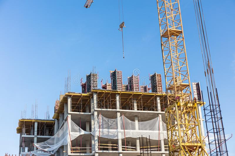 Apartment building construction site with crane against blue sky stock photos