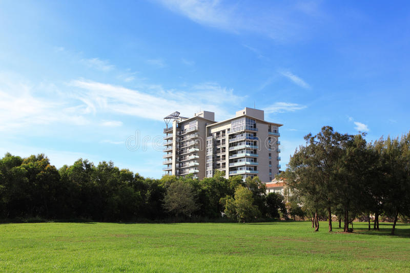 Apartment building with grass and sky stock images