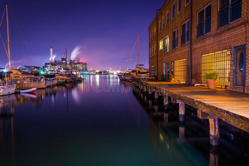 Apartment building and marina at night on the waterfront in Fell. S Point, Baltimore, Maryland royalty free stock image