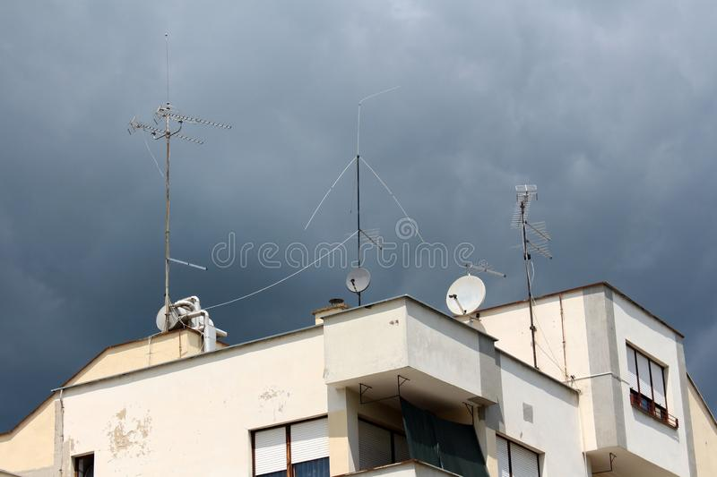 Apartment building with multiple radio and TV antennas on top mounted on strong metal poles surrounded with dark stormy blue sky. Background stock photos